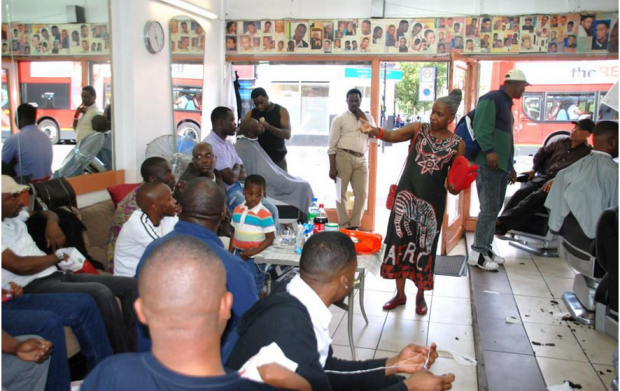 A woman speaking to a group of men and boys in a barber shop.