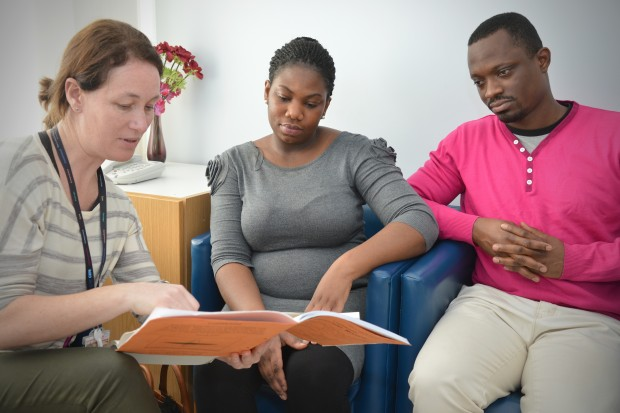 A medical professional reading through a leaflet with two people.