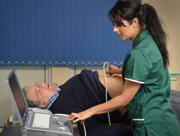 A health professional carrying out abdominal aortic aneurysm screening on a man.