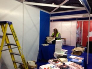 A member of staff setting up for the conference with a step-ladder nearby.