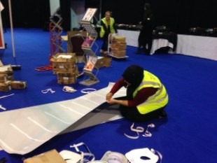Members of staff setting up for the conference using sticky tape to put posters together.