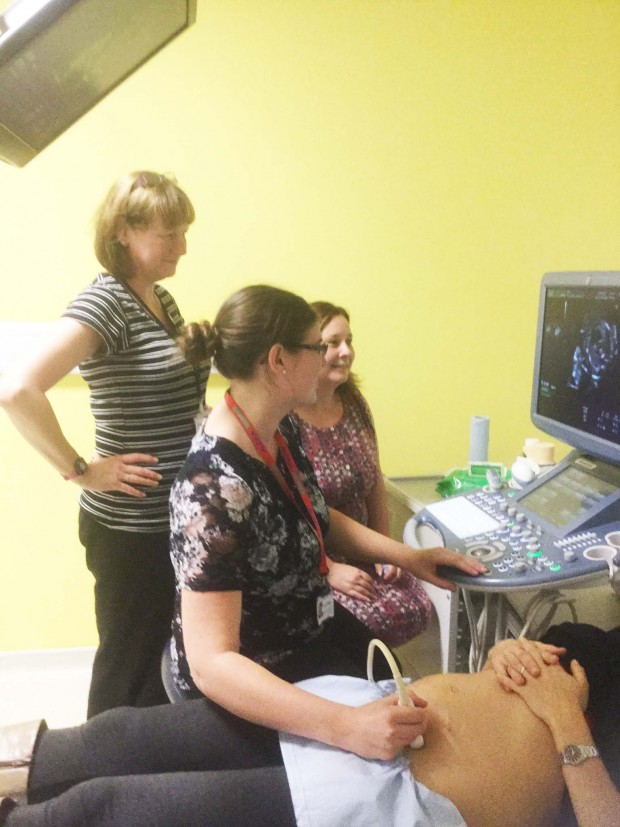 Healthcare staff practising sonography on a pregnant woman.