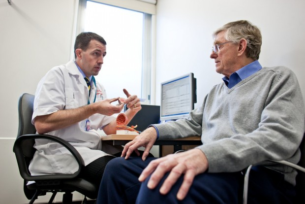 A GP talking to an older male patient.