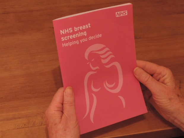 A pair of hands holding an NHS breast screening leaflet