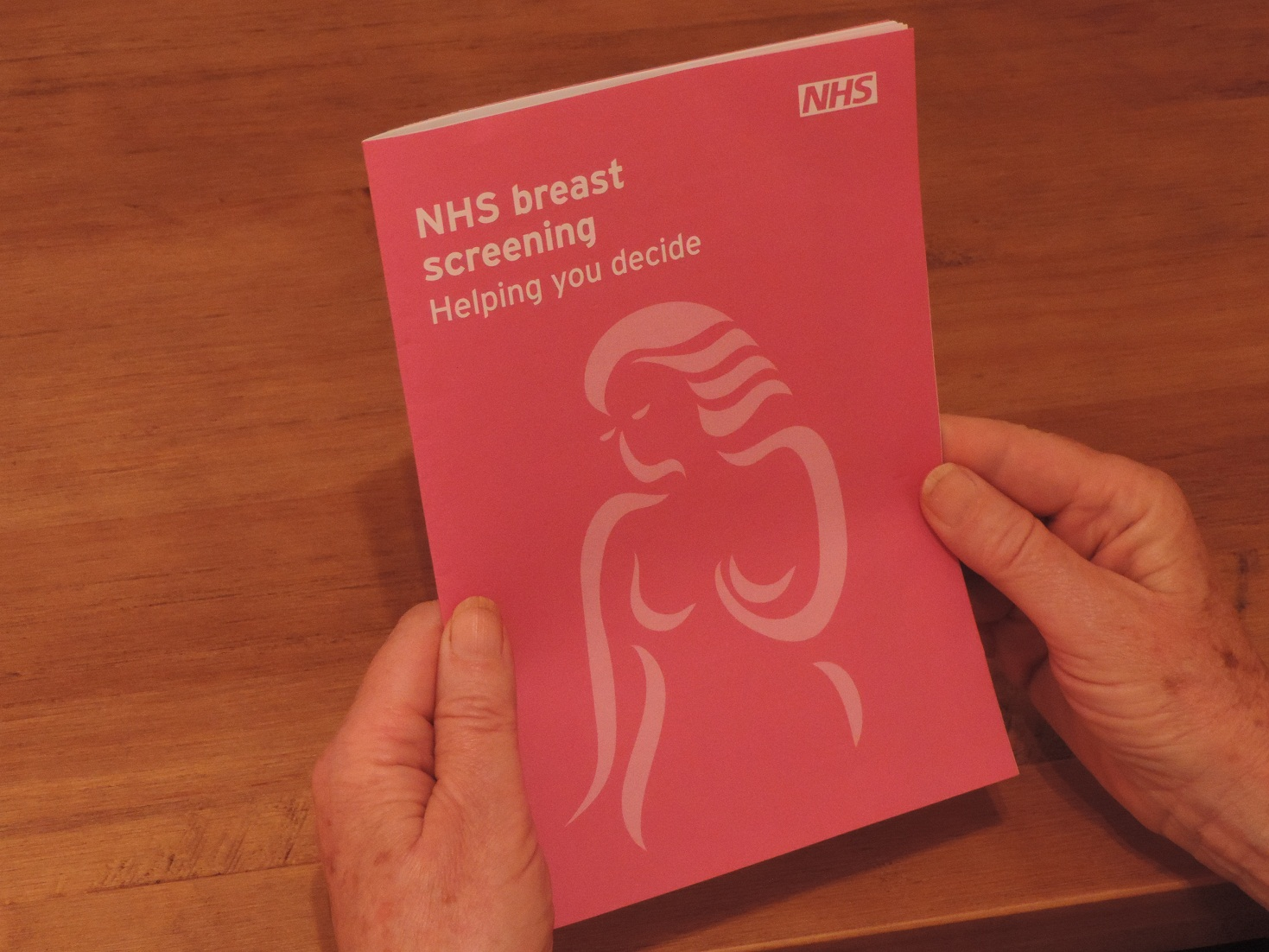 A picture of someone's hands holding an NHS breast screening leaflet.