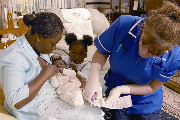 A nurse taking a blood spot sample from a newborn baby while the mother and a child comfort the baby