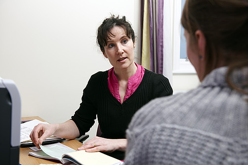 A medical professional talking to a woman, with a book in front of them.
