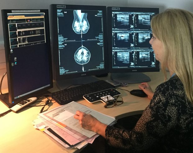 A woman reading breast screening images on several screens.