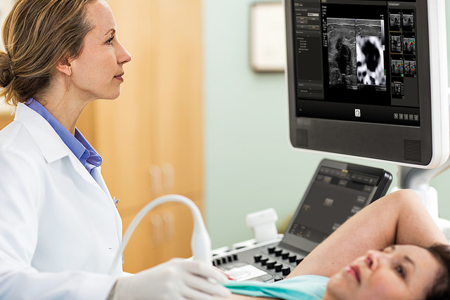 A woman having an ultrasound scan done. A medical professional is looking at the scan on a screen.
