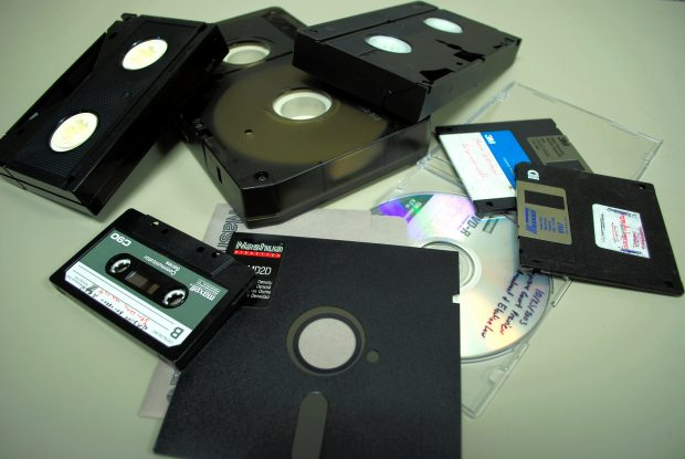 A pile of old media formats: VHS tapes, audio tapes, disk drives, floppy disks.