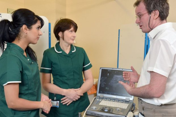 A group of medical professionals discussing a scan.