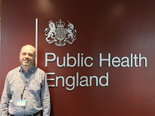 Image of Nick Johnstone-Waddell in front of the PHE logo.