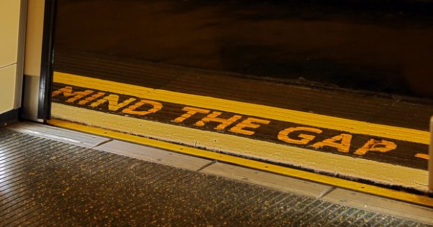 The floor of a tram or tube with the words 'mind the gap' written in bold yellow type.
