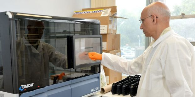 A man with a white coat works busily in a lab.