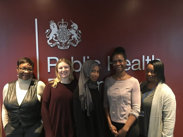 The 5 members of the helpdesk team standing in front of the PHE logo.