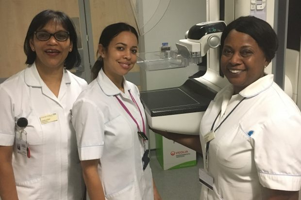 Photograph shows 3 mammographers stood in front of a machine.