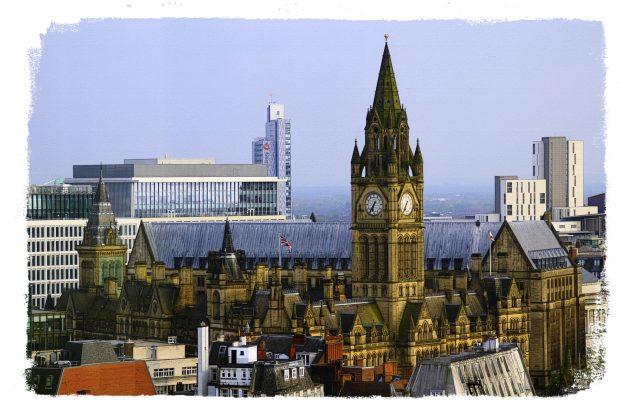 A photo of the skyline of Manchester showing the town hall and other buildings