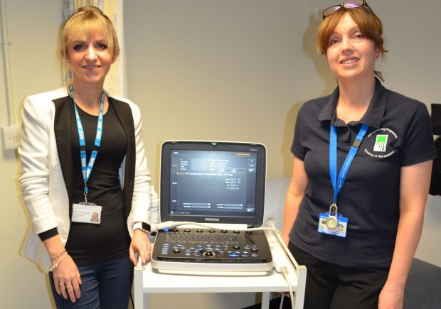 Photo of assessor Emma Wright and learner Jacquie Brennan standing by an ultrasound machine used for AAA screening tests