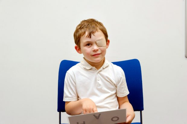 A young boy sitting in chair with an eye patch on and holding a sheet with letters on