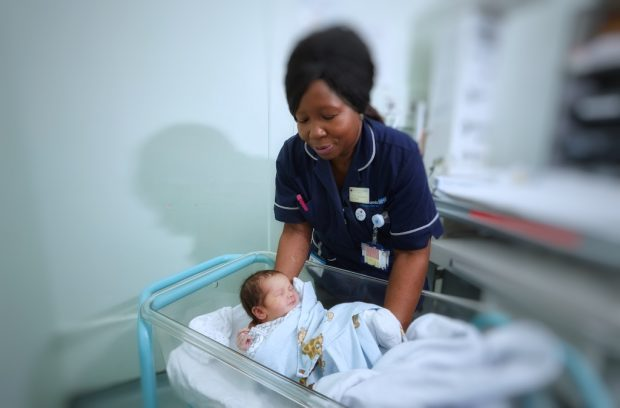 A nurse putting a newborn baby into a cot in a hospital ward