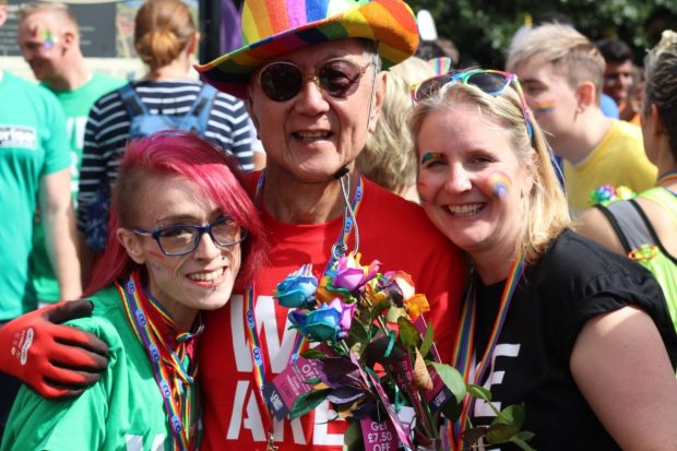 Photo shows a man and 2 women at a gay pride event in colourful clothes