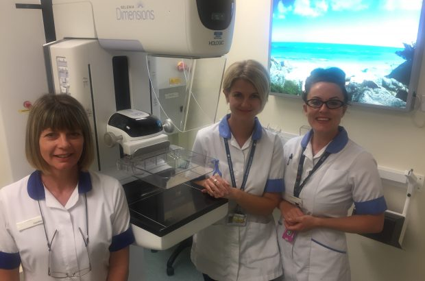 Gina Newman, right, with clinical colleagues Caroline Hanlon (senior radiographer) and Dawn Rowley (advanced assistant practitioner) in front of a breast screening machine in a clinic room