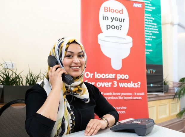 A lady on the phone smiling with information about bowel cancer in the background