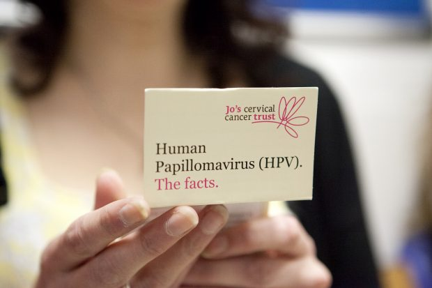 Photo shows woman holding a card with the word HPV the facts. You can see the Jo's Trust logo. The woman is blurred.