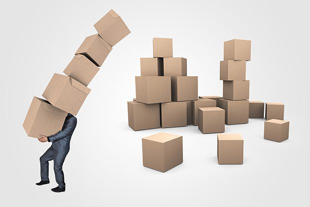 Businessman in a suit struggling under weight of carrying 5 large cardboard boxes. A pile of around 20 more boxes is behind him