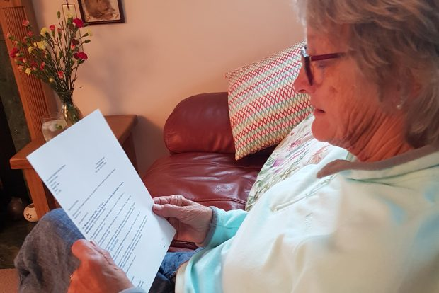 Picture of older woman sitting in a chair reading the self-referral letter