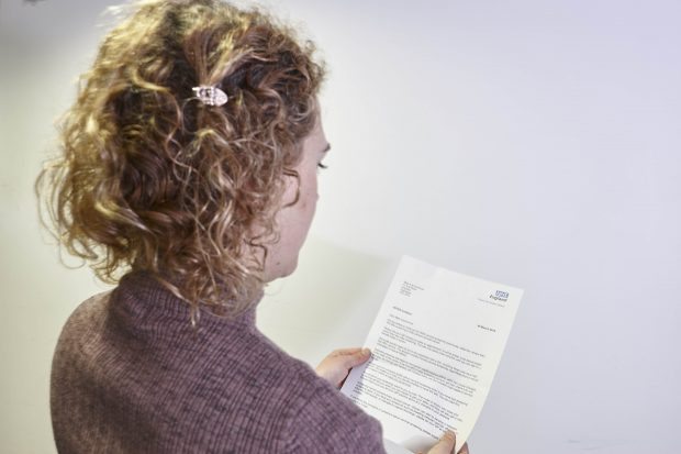 Image shows woman reading cervical screening appointment letter. You can just see the NHS logo on the top of the piece of paper..