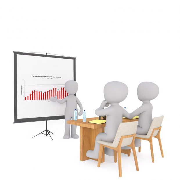 image shows a discussion between 3 individuals. One is presenting data to the other 2.