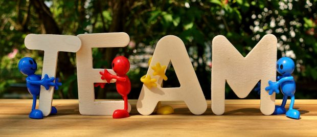 Wooden depictions of the word 'team' are being held on a table by small colourful cartoon people.