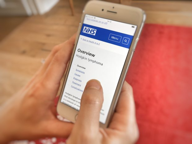 Photo shows woman's hand holding a mobile phone where she is looking up information about Hodgkin lymphoma