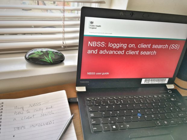 A laptop on a desk shows the words NBSS: logging on and client searches