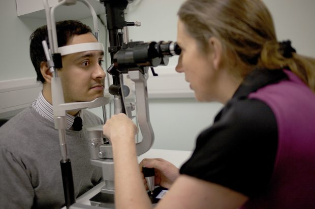 An adult man has his eyes checked by a female member of staff using a piece of equipment called a slit lamp