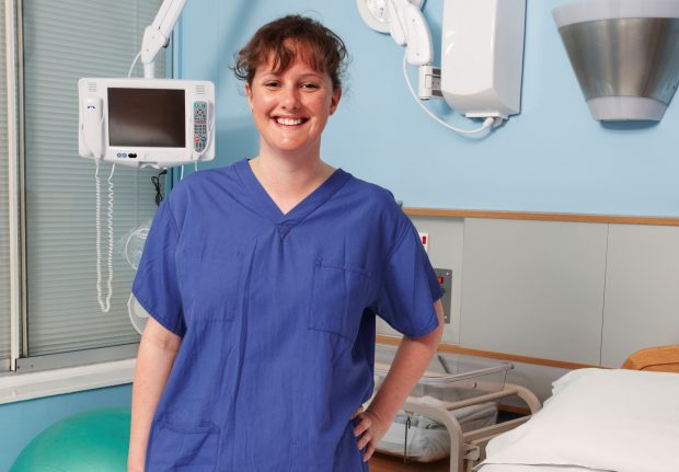 Student midwife smiling and standing by hospital bed.