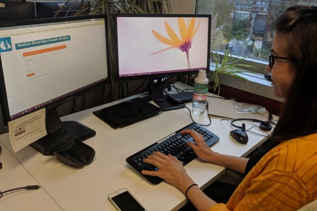 A colleague sits at her desk, logging into the NBSFS system