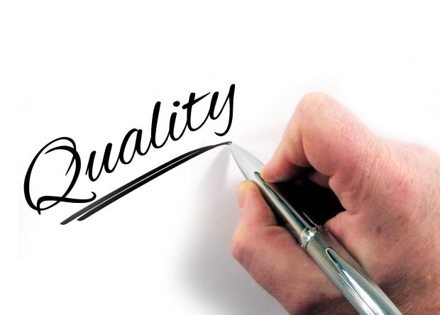 The word quality being handwritten with a pen on a piece of paper