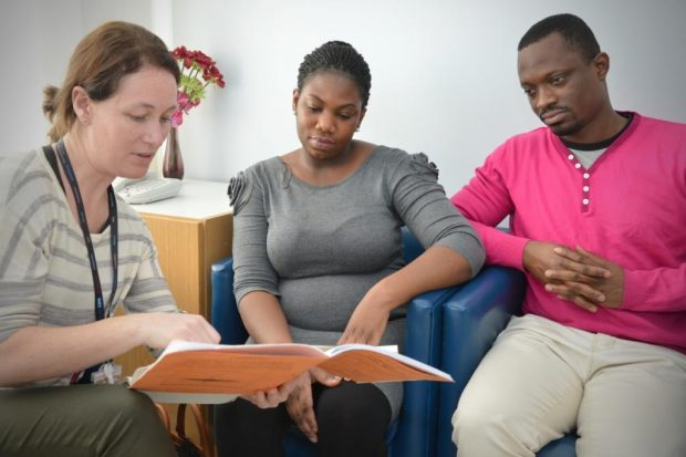 Health professional counsels young couple, showing them all looking at a booklet