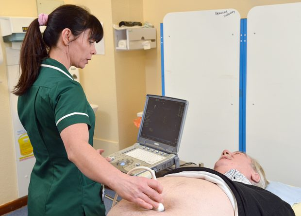 Female AAA screening technician conducts abdominal ultrasound scan on older male lying on couch