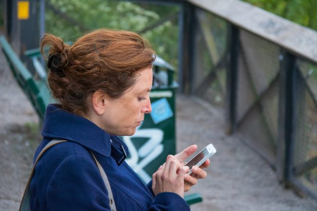 A woman sat on a bench outdoors is using her mobile phone