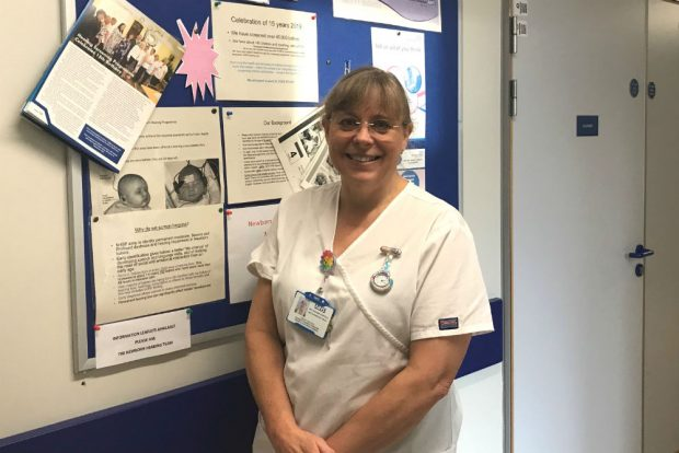 A screener, Hayley Buckley, standing in front of a notice board for newborn hearing screening