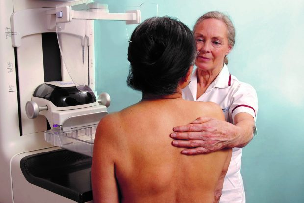 A woman having a mammogram screen taken by another woman