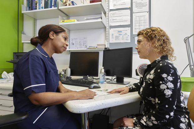 young woman talking to nurse about cervical screening
