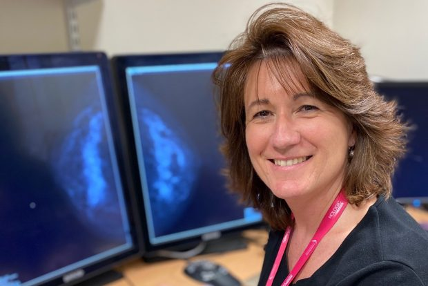 A woman smiling to camera with a breast scan on screen in the background