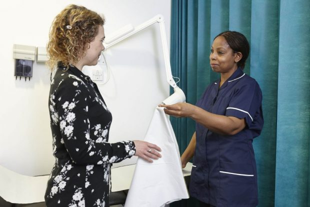 A nurse speaking to a female patient