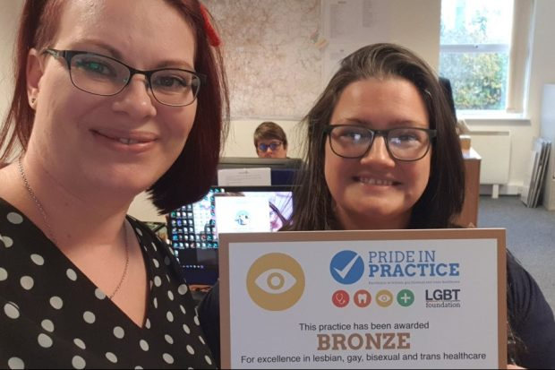 Two women (Alex Matheson and Sara Gill) holding up a certificate