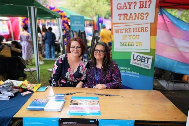 Two women (Alex Matheson and Sara Gill) sitting at a desk at a lesbian, gay, bisexual and transsexual event