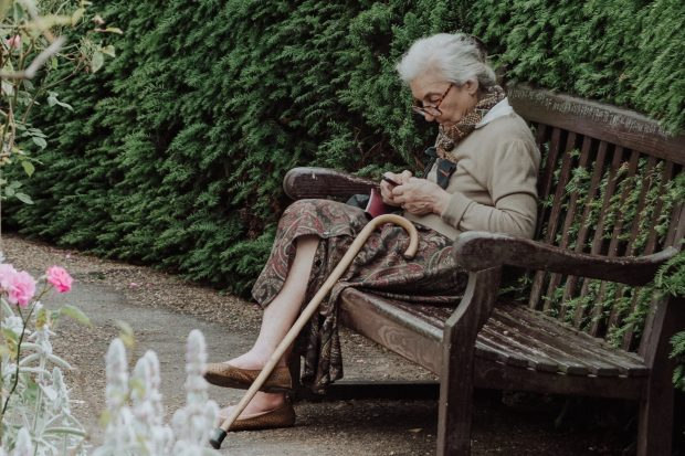 An older woman is texting while sitting on a bench